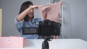 Regali unboxing della bella donna asiatica felice dalla marca o dai suoi abbonati Video femminile della registrazione di blogger  stock footage