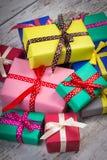 Regali variopinti avvolti per il Natale o l'altra celebrazione sulla vecchia plancia bianca Immagini Stock