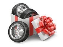 Regalo abierto de la caja de cartón del blanco con los whelles de los neumáticos de coche y el arco rojo Foto de archivo