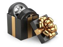 Regalo abierto de la caja de cartón del negro con los whelles de los neumáticos de coche y el arco rojo Imagenes de archivo