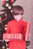 Regalo abierto de la Navidad del muchacho lindo del niño en sitio Imagen de archivo libre de regalías