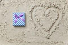 Regalo al lado del símbolo de la forma del corazón Imágenes de archivo libres de regalías