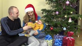 Regalo attuale allegro della donna e del padre di famiglia per il bambino nel Natale archivi video
