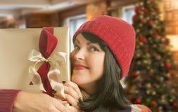 Regalo avvolto tenuta della donna nella regolazione di Natale Immagini Stock