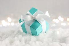 Regalo azul de la Navidad acurrucado en nieve Imagen de archivo