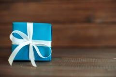 Regalo blu con il nastro su un fondo di legno Concetto del holida Fotografie Stock Libere da Diritti