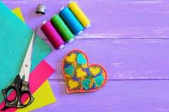 Regalo bordado del corazón para el día de tarjetas del día de San Valentín El ornamento del corazón del fieltro, hilo, tijeras, d Fotografía de archivo libre de regalías