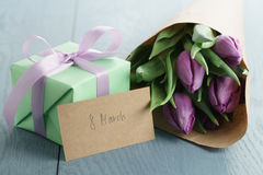 Regalo con i tulipani porpora in carta del mestiere su fondo di legno blu con la carta dell'8 marzo Immagini Stock Libere da Diritti