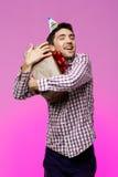 Regalo de cumpleaños feliz del abarcamiento del hombre joven en caja sobre fondo púrpura Imagen de archivo