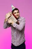 Regalo de cumpleaños feliz del abarcamiento del hombre joven en caja sobre fondo púrpura Fotos de archivo
