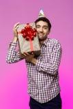 Regalo de cumpleaños feliz del abarcamiento del hombre joven en caja sobre fondo púrpura Imagen de archivo libre de regalías