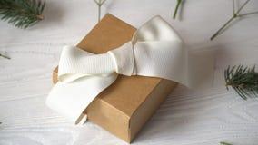Regalo de Kraft con el arco blanco y flores para la tarjeta de felicitación para el día o la boda del ` s de la tarjeta del día d metrajes