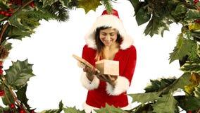 Regalo de la abertura de la mujer de Papá Noel con acebo metrajes