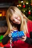 Regalo de la apertura de la muchacha el Nochebuena Fotos de archivo libres de regalías