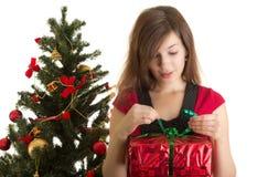 Regalo de la apertura de la mujer cerca del árbol de navidad Fotografía de archivo libre de regalías