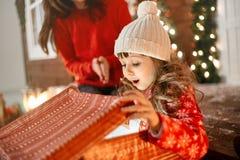 Regalo de la Navidad de la abertura de la muchacha fotos de archivo
