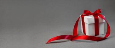 Regalo de la Navidad en la caja blanca con la cinta roja en Grey Background oscuro Bandera de la composición del día de fiesta de foto de archivo