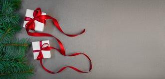 Regalo de la Navidad en la caja blanca con el fondo rojo de la oscuridad de la cinta Fotos de archivo libres de regalías