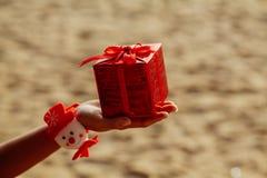 Regalo de la Navidad en caja roja en la playa Imagenes de archivo