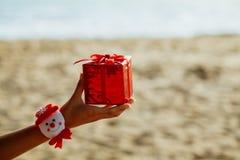 Regalo de la Navidad en caja roja en la playa Imagen de archivo