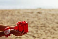 Regalo de la Navidad en caja roja en la playa Imágenes de archivo libres de regalías