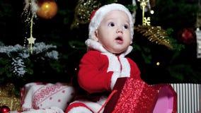 Regalo de la Navidad en las manos de un niño, él se vistió en los equipos de Papá Noel, muchacho lindo que asistía cerca del árbo almacen de video