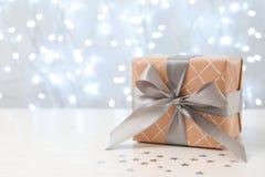 Regalo de la Navidad en la tabla contra luces borrosas foto de archivo libre de regalías