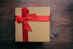 Regalo de la Navidad en una caja de oro en un fondo de madera Fotos de archivo libres de regalías
