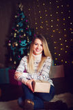 Regalo de la Navidad Mujer rubia hermosa sorprendida feliz que abre g Foto de archivo libre de regalías