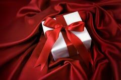 Regalo de la tarjeta del día de San Valentín en el satén rojo Imagenes de archivo