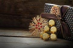 Regalo de Navidad adentro con las estrellas de la paja y las chucherías de oro en DA Imágenes de archivo libres de regalías