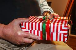 Regalo de Navidad brillantemente envuelto en manos de un más viejo hombre - primer y foco selectivo imagen de archivo