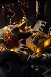 Regalo de Navidad con el suéter hecho punto, las luces de la Navidad y dos vidrios de vino Foto de archivo