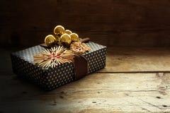 Regalo de Navidad con las estrellas de la paja y las chucherías de oro en el ru oscuro Fotos de archivo