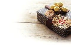 Regalo de Navidad con las estrellas de la paja y las chucherías de oro en rústico Fotos de archivo libres de regalías