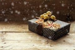 Regalo de Navidad con las estrellas de la paja y las chucherías de oro en un rusti Foto de archivo