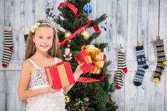 Regalo de Navidad de la abertura del adolescente cerca del árbol del Año Nuevo Fotografía de archivo