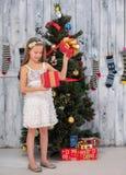 Regalo de Navidad de la abertura del adolescente delante del árbol del Año Nuevo Imagen de archivo libre de regalías