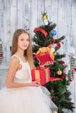 Regalo de Navidad de la abertura del adolescente delante del árbol del Año Nuevo Imágenes de archivo libres de regalías
