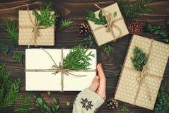 Regalo de Navidad de la abertura Woman& x27; s da sostener la caja de regalo adornada en la tabla de madera rústica Foto de archivo