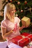 Regalo de Navidad de la apertura de la mujer delante del árbol Fotos de archivo