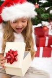 Regalo de Navidad emocionado de la apertura de la niña Fotografía de archivo