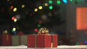 Regalo de Navidad en piso cerca del árbol mágico chispeante de Navidad, víspera del día de fiesta almacen de video