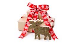 Regalo de Navidad en rojo con alces o un reno hechos a mano de madera Fotos de archivo libres de regalías
