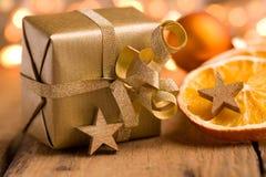 Regalo de Navidad de oro lindo en la madera Imagen de archivo libre de regalías