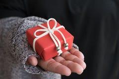 Regalo de Navidad, primer de la caja de regalo de la Navidad Mujer que sostiene sma Foto de archivo libre de regalías