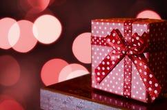 Regalo de Navidad punteado en el fondo borroso de las luces Imagen de archivo libre de regalías