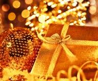 Regalo de oro de la Navidad con las decoraciones de las chucherías Imagen de archivo libre de regalías