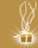 Regalo de oro de la Navidad con los rayos ligeros Fotos de archivo