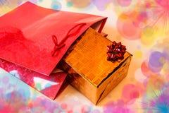 Regalo de oro en bolsa de papel roja Imagen de archivo